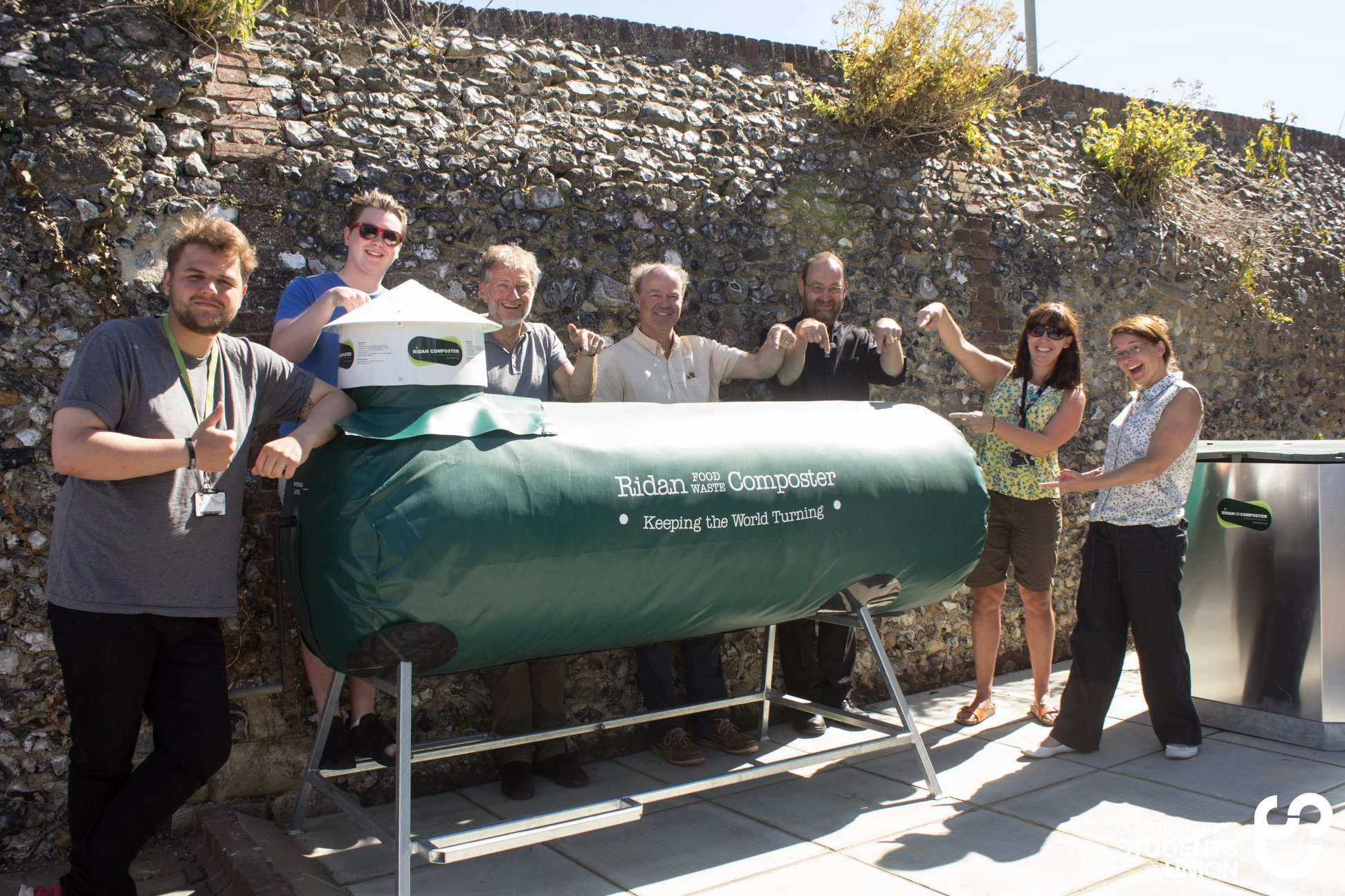 group of people stood around a Ridan composting machine